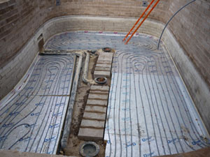 Underfloor heating lines installed into the pond base before the final base will be cast to enclose these pipe lines and the bottom drains.