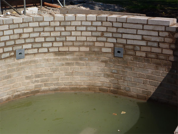 This shows angled return lines fitted flush against the pond walls for cladding later.